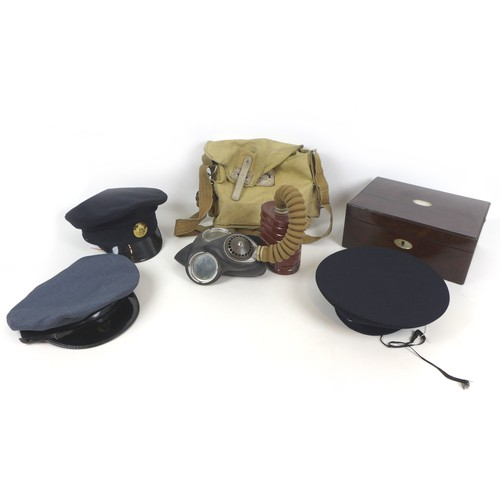 68 - A WWII Mk 4 gas mask bearing '1940' an associated cloth case, three military caps, and a Victorian r...