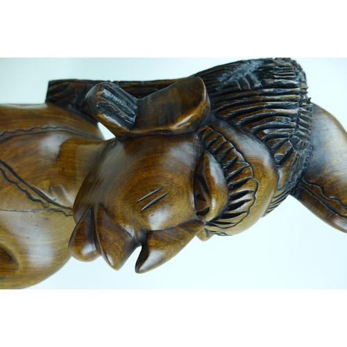 34 - Two modern African carvings, one carved as a mask with headdress, 28 by 16.5 by 48.5cm long, the oth...
