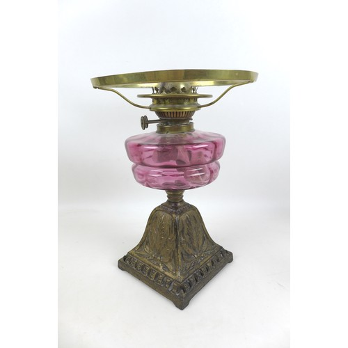 48 - A Victorian paraffin lamp, with cranberry glass reservoir, base 23 by 33cm high, etched clear glass ...