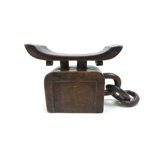 144 - A West African carved wooden neck rest, 19th century, the neck rest with two lines of chip carved de...