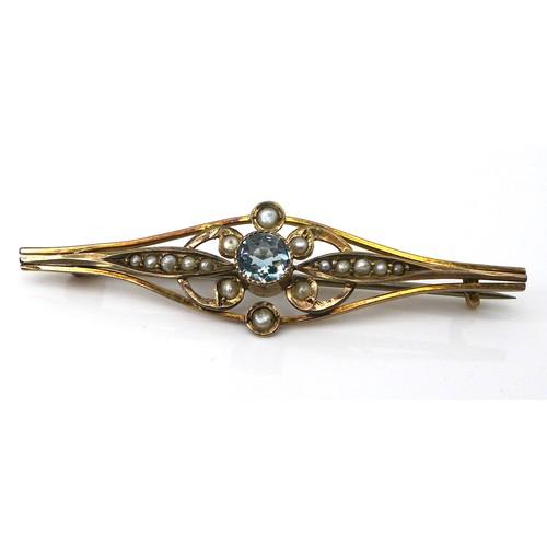 323 - An Edwardian 9ct gold, aquamarine, and seed pearl bar brooch, the central brilliant cut stone, 4.5 b...