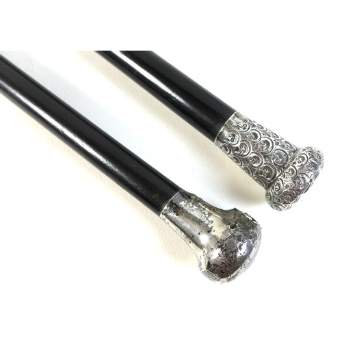 69 - Two George V silver topped ebonised canes, one with a repousse wave patterned handle, and a silver t...