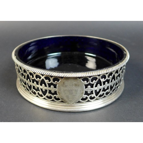 70 - A George III silver wine coaster, with bead rim, pierced floral decorated sides with an armorial mar...