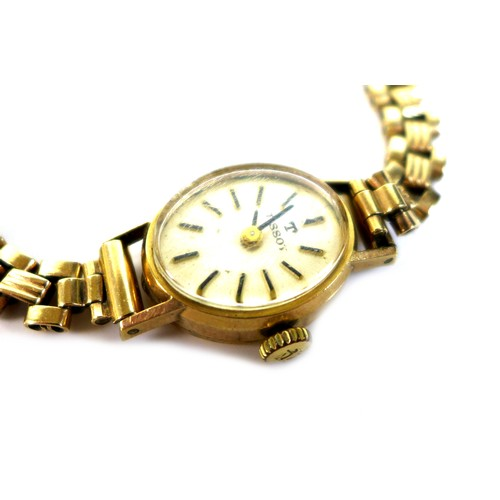 217 - A vintage Tissot 9ct gold lady's wristwatch, on a 9ct bracelet strap, oval brushed gold dial with go...