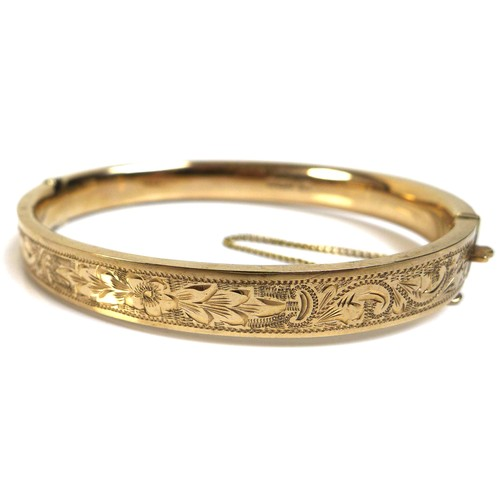 339 - A 9ct gold bangle, with floral bright cut engraved decoration, complete with safety chain, 13.2g tot...