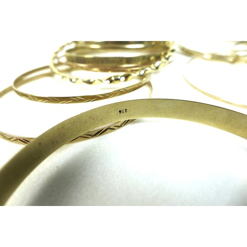 407 - A group of twenty 9ct gold bangles, all marked, total weight 81.3g, together with four unmarked yell...
