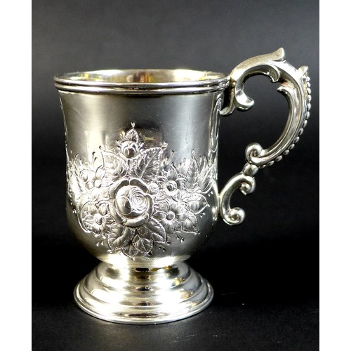 80 - An Anglo Indian colonial silver christening tankard, with repousse Rococo style floral decoration in...