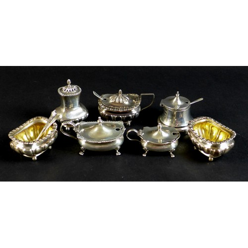 89 - An Edwardian silver cruet set of gadroon bellied cauldron form, with fluted rims and silver gilt int...