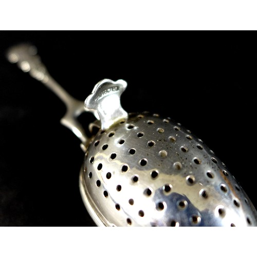 36 - An Edward VII silver tea infuser, fancy scroll decorated handle with two pronged support to the two ...