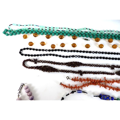 327 - A collection of necklaces and bangles, including butterscotch amber, coral, plastic, faux pearls, a ...