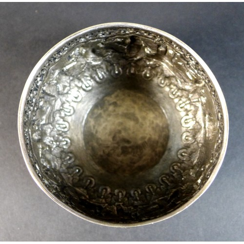 24 - An early 20th century Burmese white metal bowl, intricately repousse decorated and chased with a con...