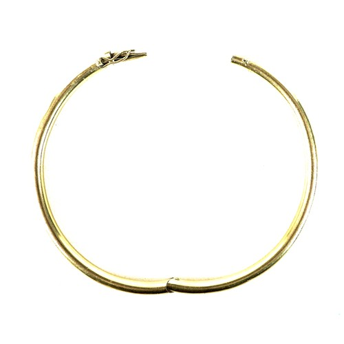 324 - A 14ct gold bracelet of fixed hinged form, likely Continental early 20th century, circular hollow se...