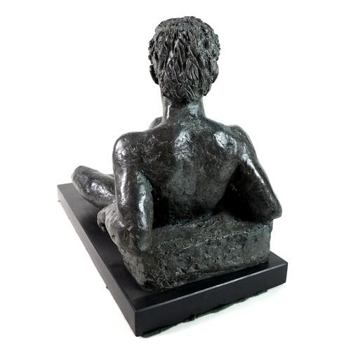82 - Karin Jonzen FRBS (British, 1914-1998): 'Reclining Youth', a bronze figural sculpture with a green p...