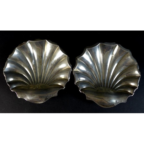 38 - A pair of Edward VII silver dishes, of shell form raised on three ball feet, Atkin Brothers, Sheffie...