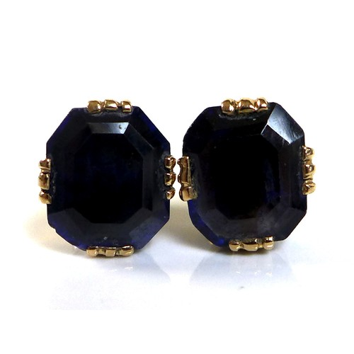 130A - A pair of synthetic sapphire earrings, the deep blue emerald cut 'stones', 9 by 7.7mm, set in yellow...