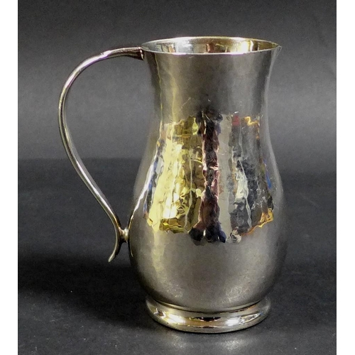24 - An ERII silver milk jug with planished finish, Howard Jesse Brown, London 1952, 8 by 5.5 by 9cm high...