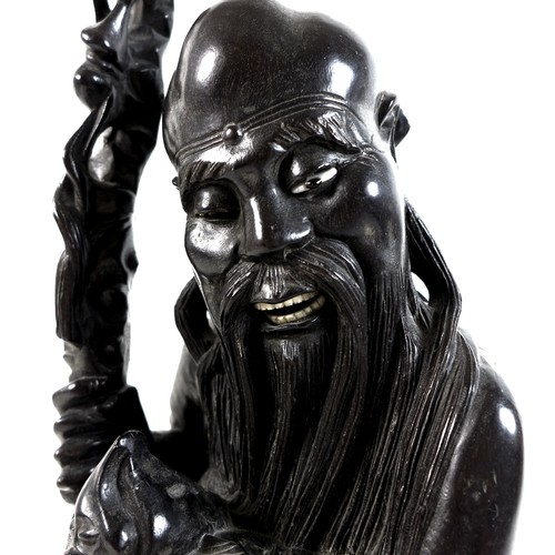20 - A Chinese hardwood carving of Shao Lao, Qing Dynasty, holding an ornately carved staff and a flaming...