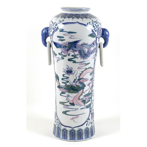 23 - A modern Chinese porcelain vase, of tall slender form, decorated with panels depicting a dragon chas...