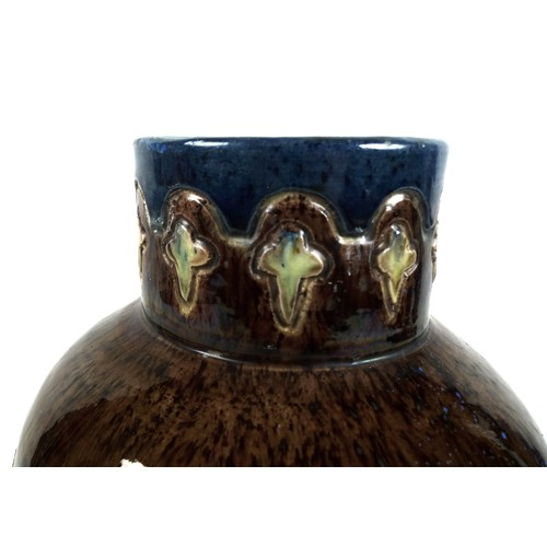 82 - An Art Nouveau pottery vase, with stylised flowers incised into the body, over glazed in majolica ma...