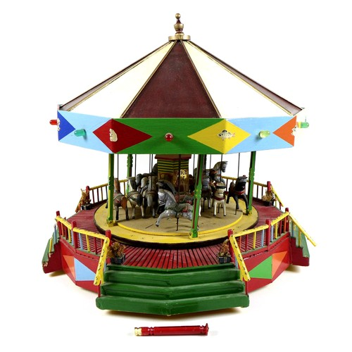 197 - A vintage moving model of a fairground carousel, with detailed modelling and decoration, likely buil...