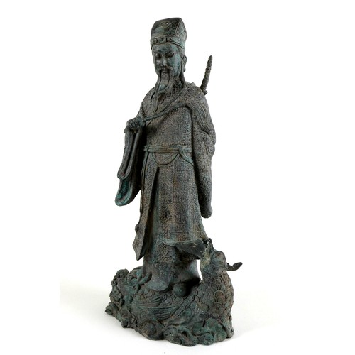 19 - A cast metal sculpture, modelled as the Daoist figure Lu Dongbin standing on a sea monster, with swo...