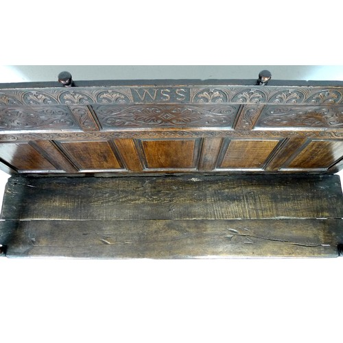 375 - A 17th century provincial oak settle, the rectangular back with a decorative frieze and three panels...