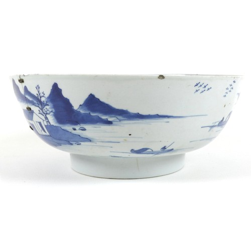 14 - A Chinese porcelain blue and white bowl, Qing Dynasty, 18th century, the body painted with houses in...