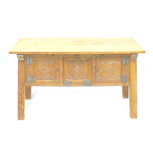 371 - An Arts & Crafts oak sideboard, rectangular surface over three carved panel doors to the front, rais...