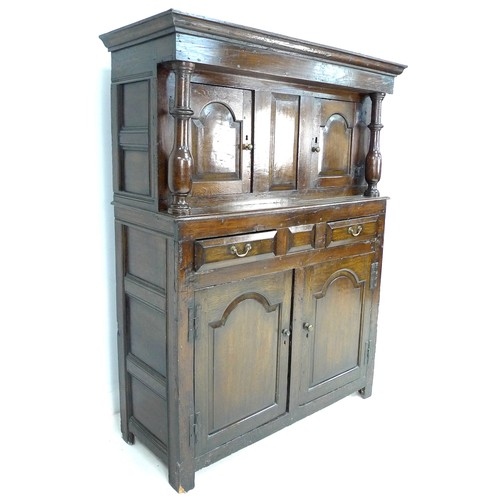 379 - An 18th century oak court cupboard, the cornice supported on two baluster columns, two small arched ...