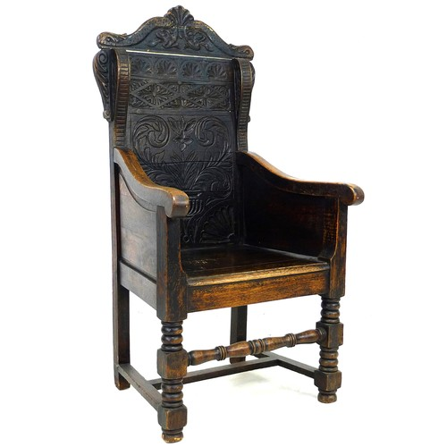 373 - An oak Wainscot type armchair, 19th century with some 17th century parts, the solid back carved with...