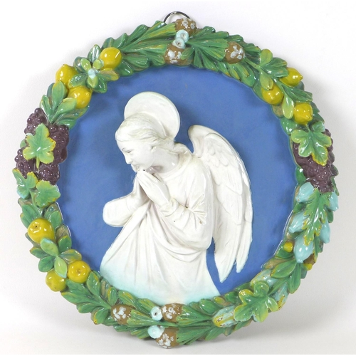 12 - A Continental 'Della Robbia' faience and terracotta relief plaque, depicting an angel in prayer, wit...