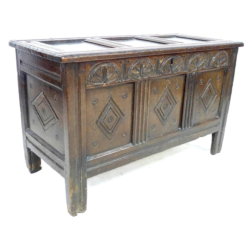 236 - A 18th century oak chest, with three panelled front, lift lid, carved with diamond shapes below a pa...