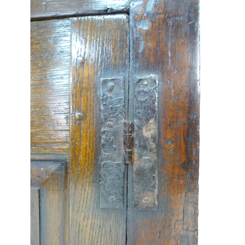 240 - An 18th century oak court cupboard, the cornice supported on two baluster columns, two small arched ...