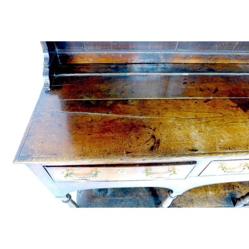 242 - A large George III oak Welsh dresser, cornice over a closed three shelf waterfall plate rack, the ba...