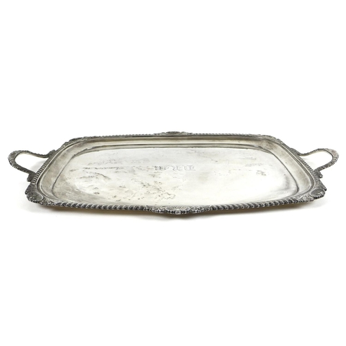 78 - A large Edward VII silver twin handled serving tray, with gadrooned and shell clasped rim, the centr...