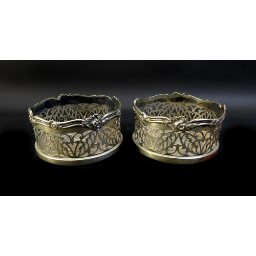 1 - A pair of silver plated bottle coasters, foliate pierced sides and applied ribbon and foliate rims, ...