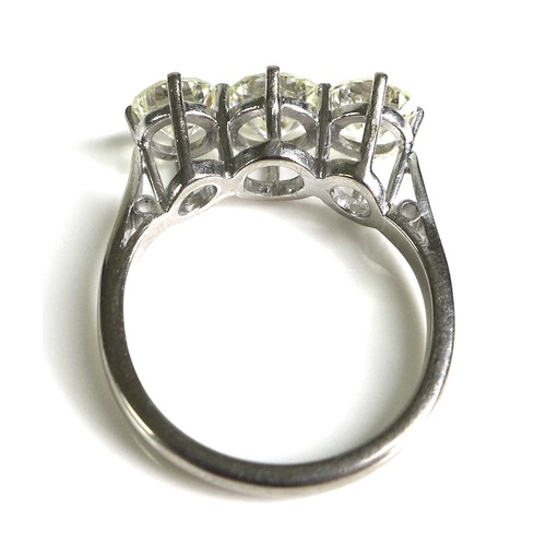 254 - An 18ct white gold and diamond three stone ring, the high claw set central brilliant cut stone, 6.7 ...