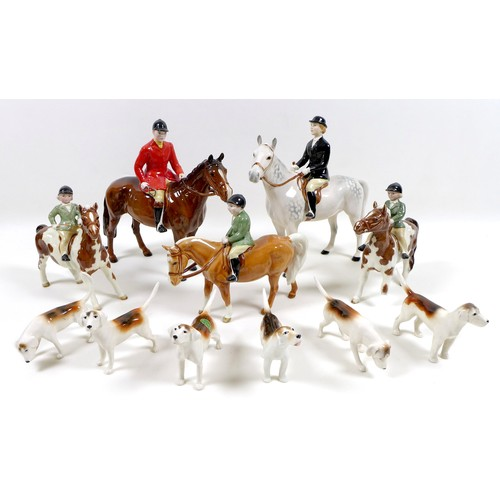 A Beswick Hunting Family Group, comprising 'Huntsman', style two, standing, model 1501, brown gloss, 21cm high, 'Huntswoman', style two, standing, model 1730, grey gloss, 21cm high, two 'Girl on Pony', model 1499, skewbald gloss, one a/f with damaged legs, each 14cm high, 'Boy on Pony', model 1500, palomino gloss, 14cm high, and six Foxhounds, models 941, 942, 2263, 2624, and 2265, white, tan and black gloss, each approximately 7cm high. (11)