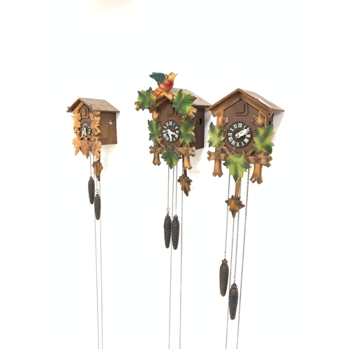 436 - A near pair of West German cuckoo clocks, together with a close match cuckoo clock