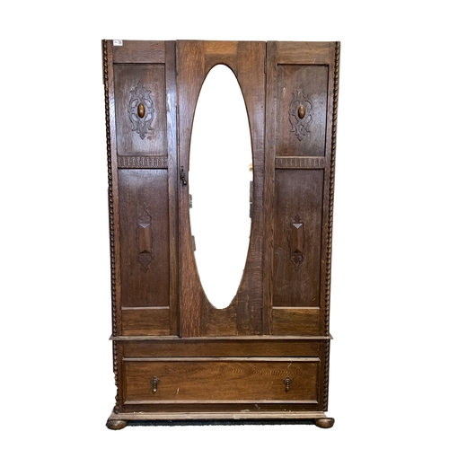 440 - Early 20th century oak single wardrobe, with bevelled oval mirror enclosing interior fitted for hang...