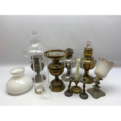 698 - Various brass and other oil lamps, some with glass chimneys and shades, in one box