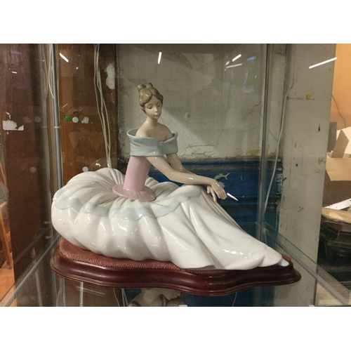 61 - Large Nao figurine of lady sitting with stand...