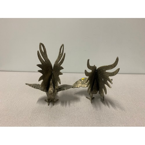 31 - Pair of white metal fighting cockerel figures.