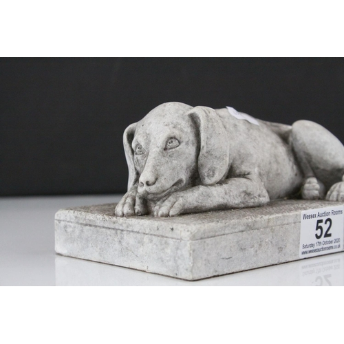 52 - A stone effect scuplture of a recumbent dog....