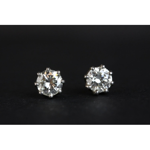 13 - Pair of diamond solitaire stud earrings, each round brilliant cut diamond weighing approx 1.0 carat,...