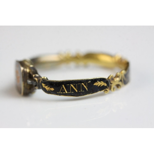 16 - George III black enamelled yellow metal mourning ring, the central panel with gilt intaglio depictin...