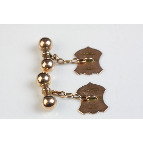 33 - Pair of 9ct rose gold chain link cufflinks, the shield shaped panel with engraved floral and foliate...