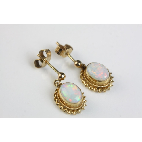 48 - Pair of opal 9ct yellow gold drop earrings, the precious white opal displaying violet, indigo, green...