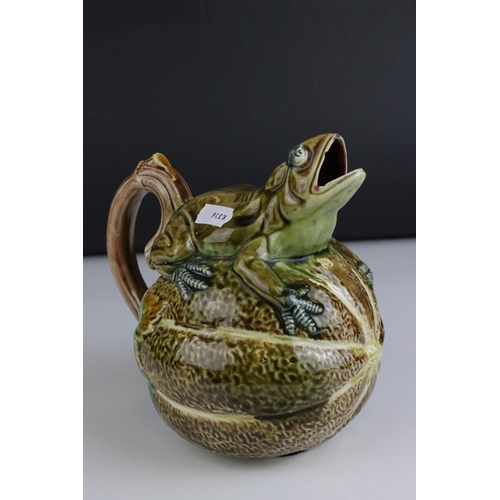 25 - A majolica style jug in the form of a seated frog on a melon or piece of fruit.