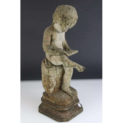 56 - A composite stone classical  figure of a child seated on a wall reading book.